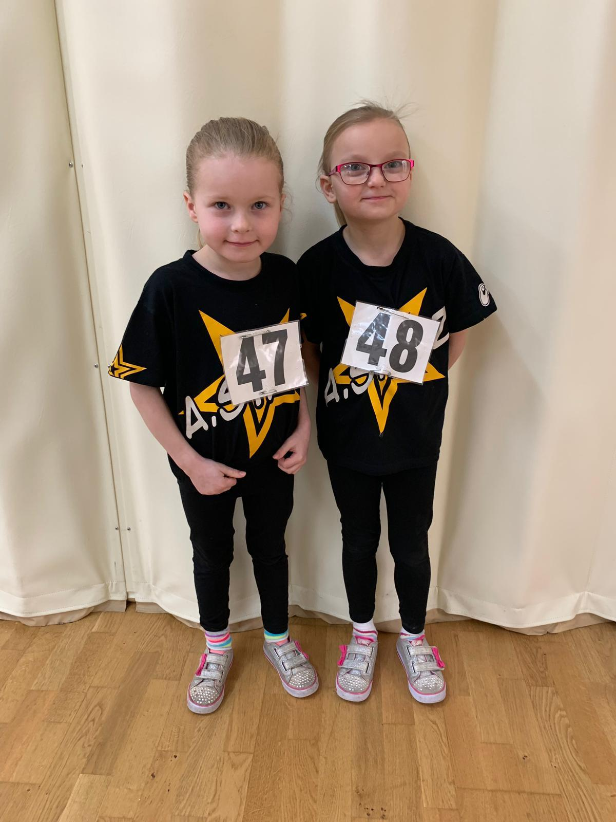 Two girls wearing A Stars t-shirts and exam numbers
