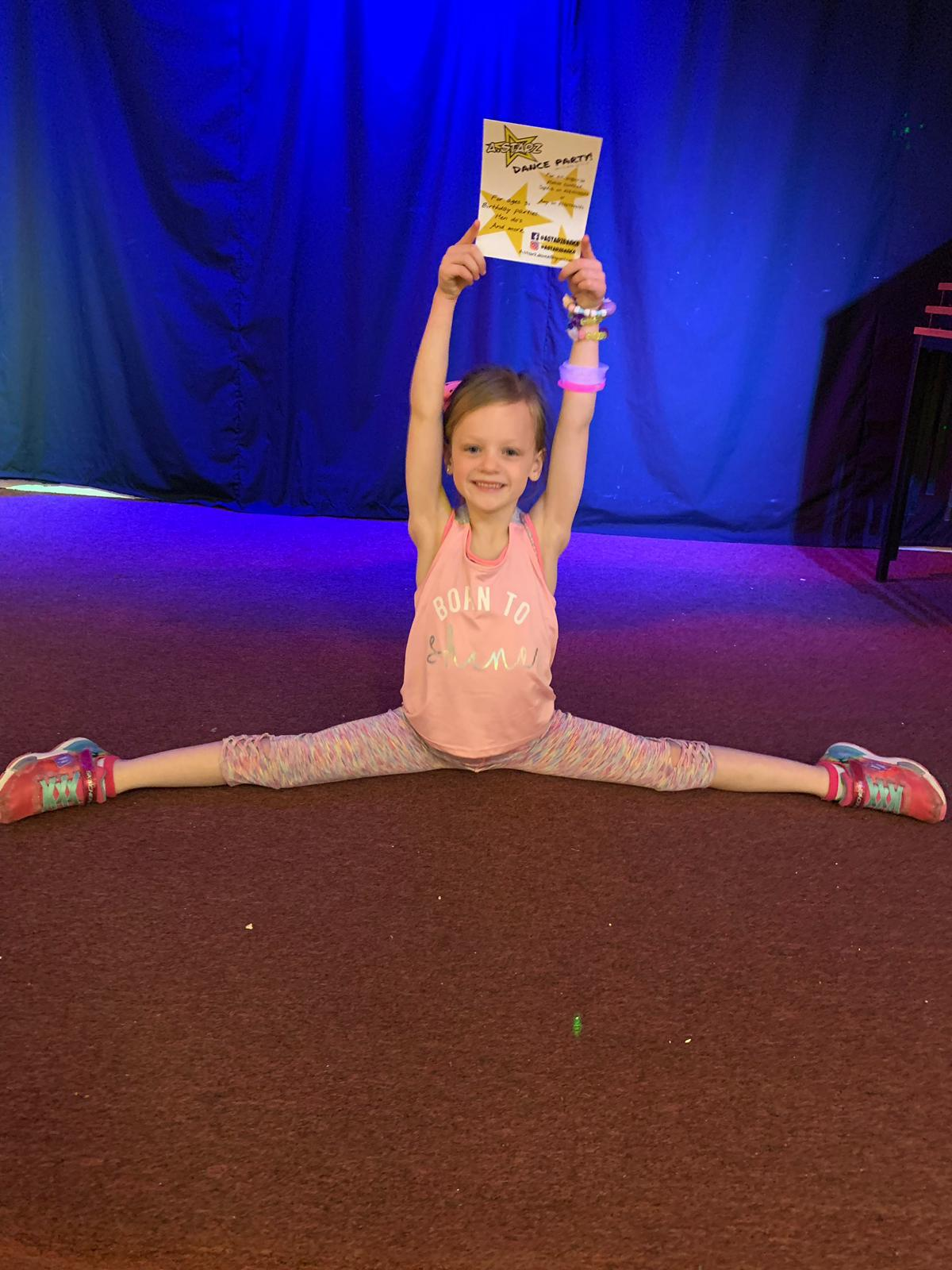 A girl doing side splits and holding a dance party certificate in the air